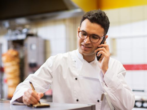 people, fast food and cooking concept - chef at kebab shop writing order and calling on smartphone