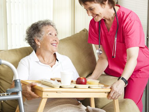 Retired senior woman in nursing home gets lunch from a caring nurse.
